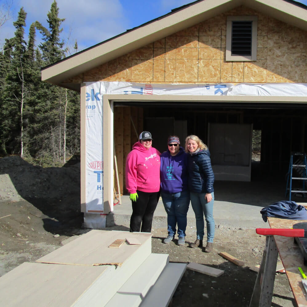 Three women standing in front of a house in construction